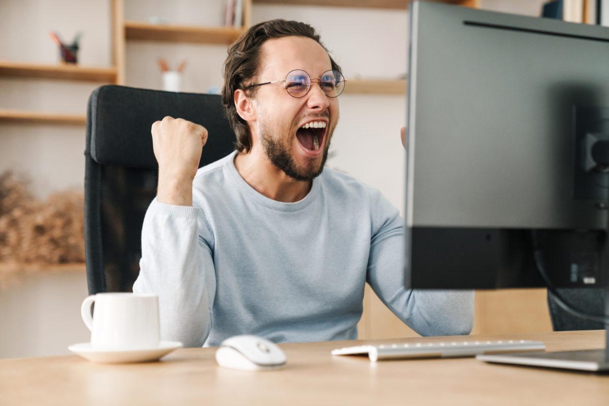 パソコンの前でガッツポーズする男性