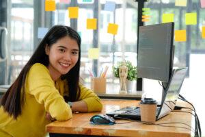 パソコンの前でこちらへ微笑む女性